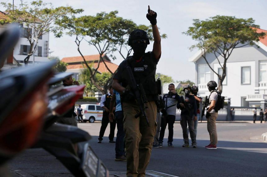 Anti-terror policemen stand guard following a bomb blast at police office in Surabaya, Indonesia, on May 14, 2018.
