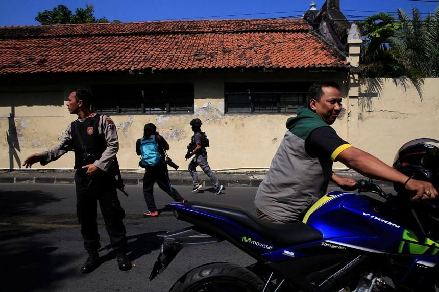 An anti-terror policeman runs following a blast at a police office in Surabaya, Indonesia, on May 14, 2018.