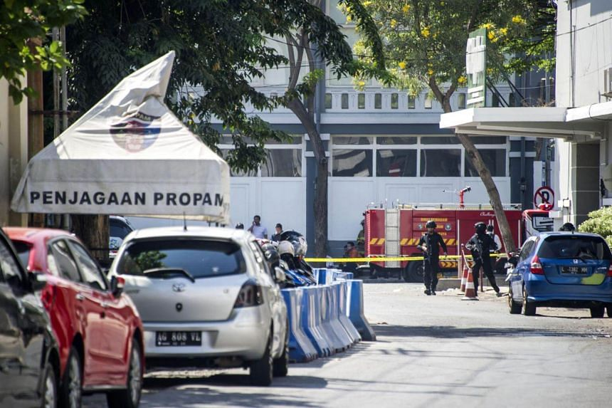 Mobile brigade police patrol around the Surabaya police headquarters following a suicide attack in Surabaya, on May 14, 2018.