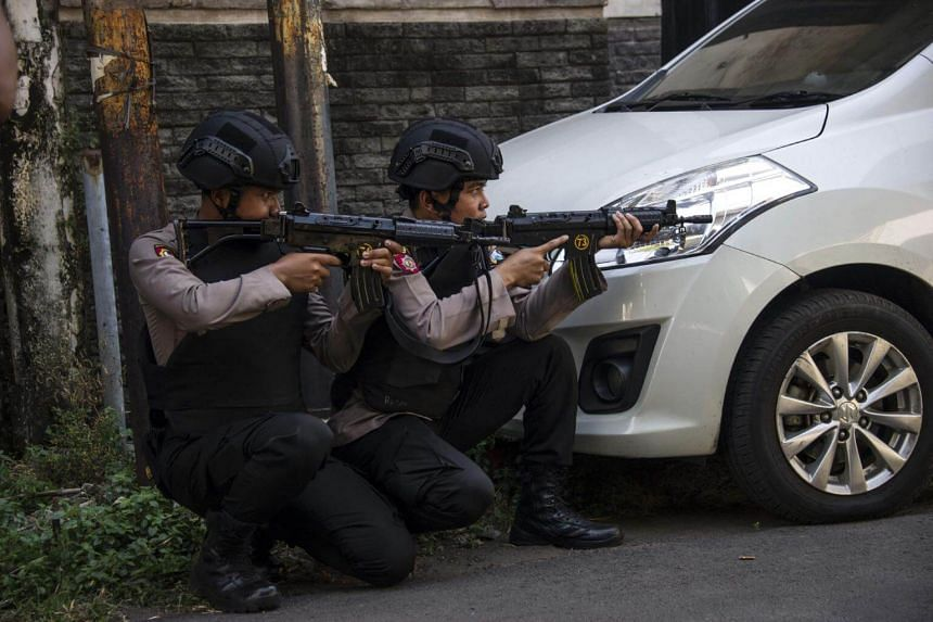 Mobile brigade police take position as they patrol outside the Surabaya police headquarters following a suicide attack in Surabaya, on May 14, 2018.