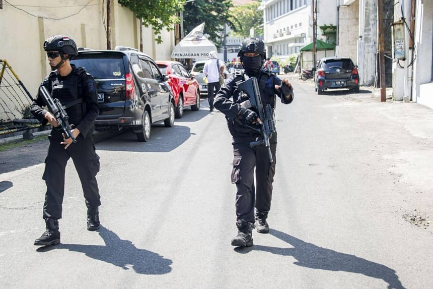 Mobile brigade police patrol around the Surabaya police headquarters following a suicide attack in Surabaya, on May 14, 2018.