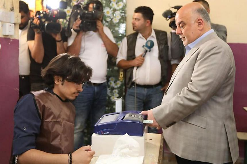 PM Haider al-Abadi having his biometric voting card checked with his fingerprint upon arriving at a poll station in the capital Baghdad's Karrada district on May 12, 2018.