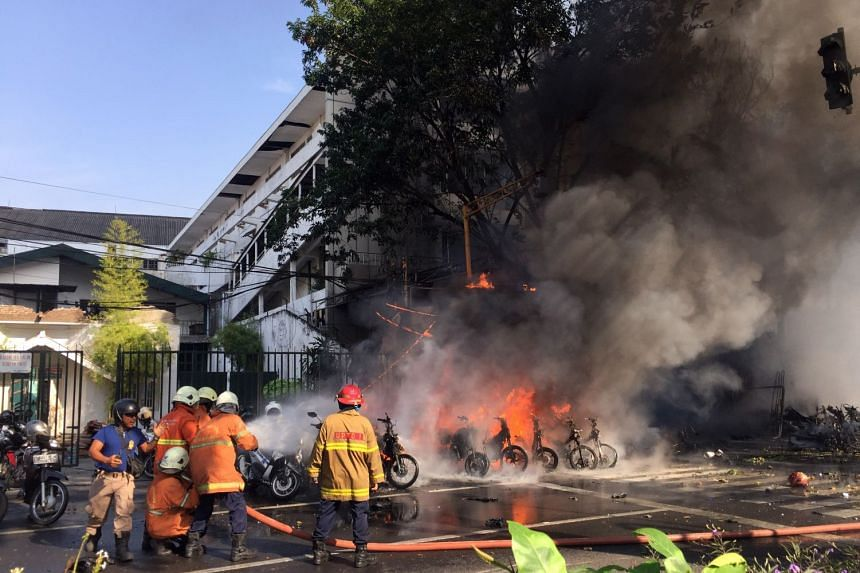 Firemen extinguishing vehicles on fire shortly after a bomb blast at a church in Surabaya, East Java, Indonesia, on May 13, 2018.