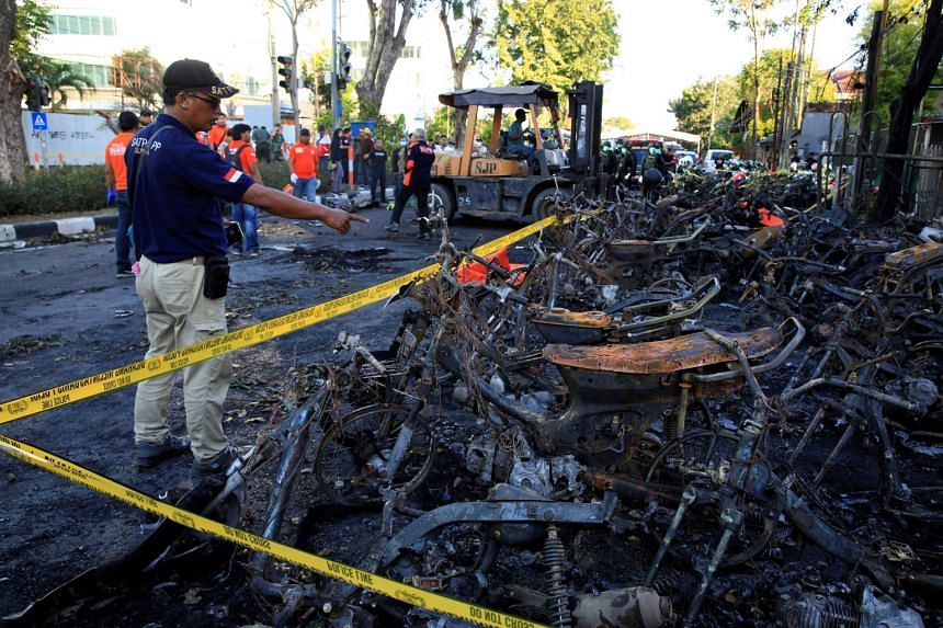 A forensic police officer points at burned motorcycles following a blast at the Pentecost Church Central Surabaya (GPPS), on May 13, 2018.
