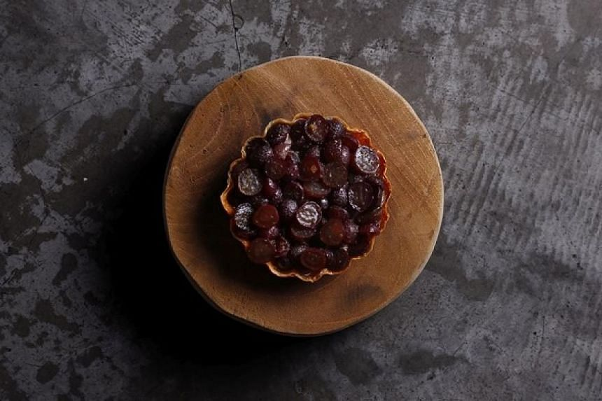 A yuba-skin pastry tart filled with creamy, light chicken parfait and crowned with slices of pickled grape.