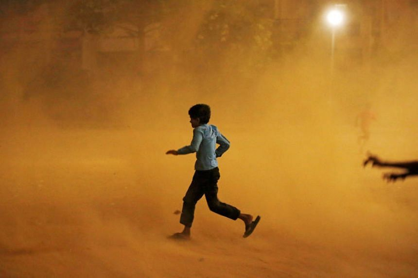 A boy runs for cover during a dust storm in New Delhi on May 13, 2018.