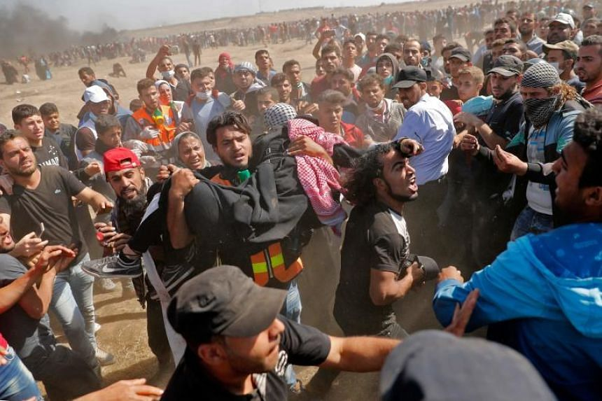 Palestinians carry a demonstrator injured during clashes with Israeli forces near the border between the Gaza strip and Israel east of Gaza City, on May 14, 2018.