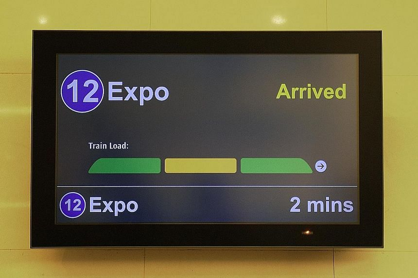 The new Passenger Load Information System display at Downtown MRT station. The new screens (right) have three colour codes: Green means the car is not packed, while amber means only standing space is available. The third colour, red, means there is l