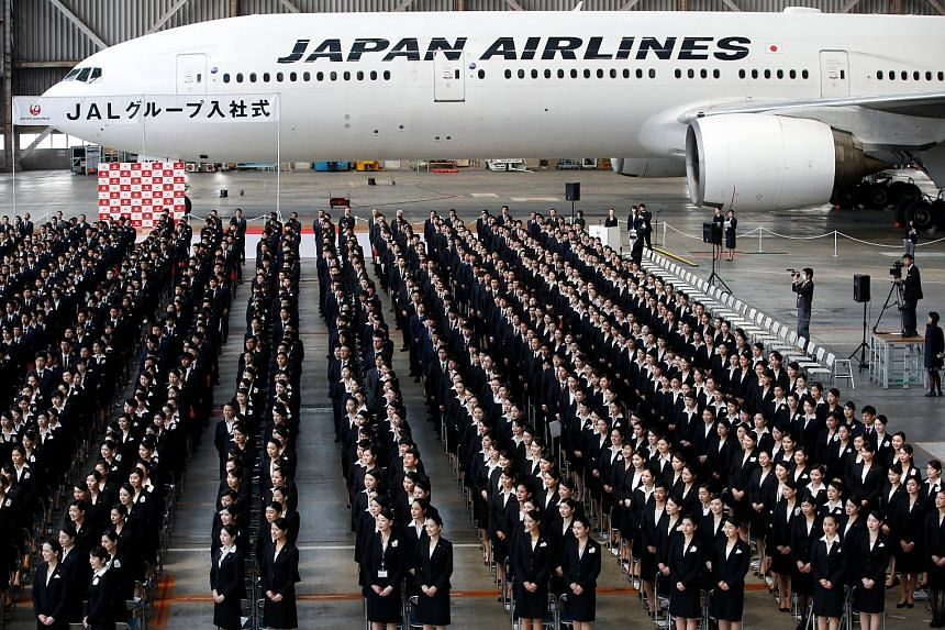 Newly hired employees of Japan Airlines at the group's initiation ceremony in a hangar of Haneda Airport in Tokyo last month. The group is eyeing a larger slice of the budget air travel market, which has been slow to take off in Japan relative to oth