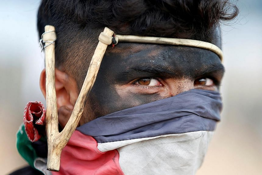 A Palestinian demonstrator with a slingshot at a mass protest at the Israel-Gaza border east of Gaza City yesterday. Tens of thousands had streamed to Gaza's land border, some approaching the Israeli fence - a line Israeli leaders said Palestinians w