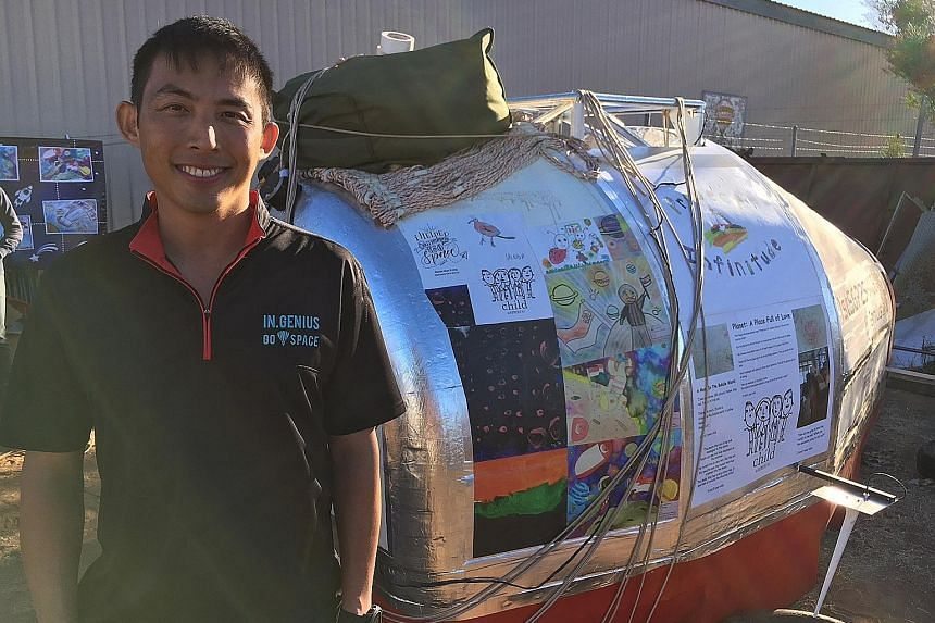 Singaporean air force pilot Yip Chuang Syn with the launch capsule in Alice Springs in central Australia yesterday. On the craft is artwork by children from Haig Girls' School and Child at Street 11, a childcare centre in Ang Mo Kio. Maj Yip was due
