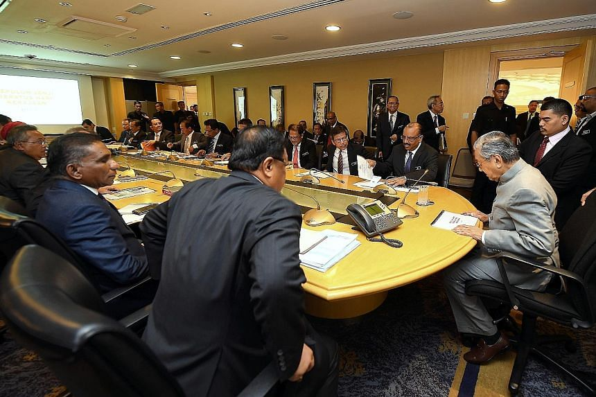 Above: The Malaysian Anti-Corruption Commission said its former head Dzulkifli Ahmad's contract has ended. Left: Prime Minister Mahathir Mohamad and Chief Secretary Ali Hamsa (on Tun Dr Mahathir's right) at a meeting with senior civil servants in Put