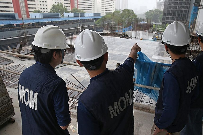 Above: Workers at a worksite in Dundee Road, where MOM held a surprise inspection yesterday. Left: MOM inspection officers conducting checks at the worksite, which was found to have several work-at-height issues. MOM will be issuing the contractor a
