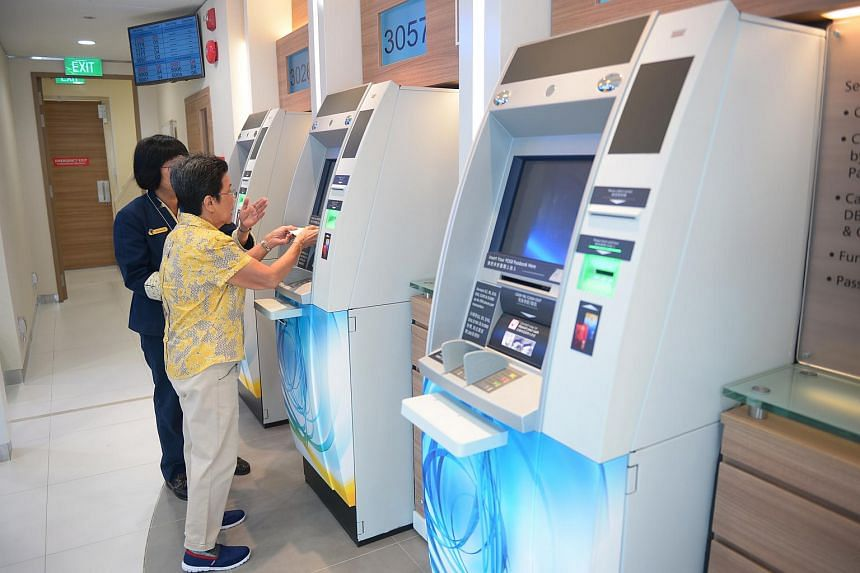 A file photo of a POSB bank officer helping an elderly woman with her banking transactions at a Branch Machine (BM).