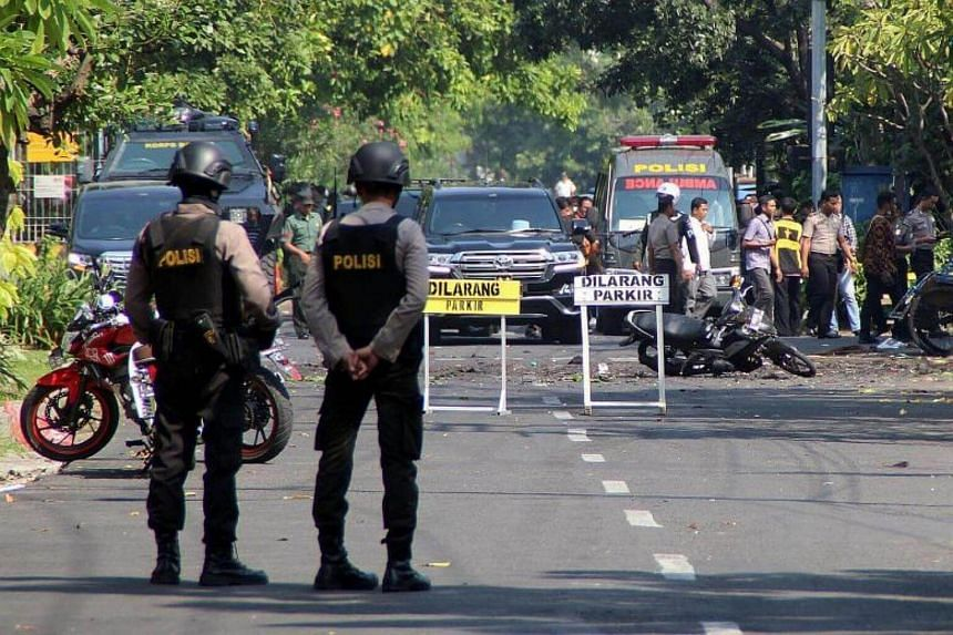 Indonesian bomb squad officers inspecting the blast site in front of the church in Surabaya, East Java, Indonesia, on May 13, 2018.