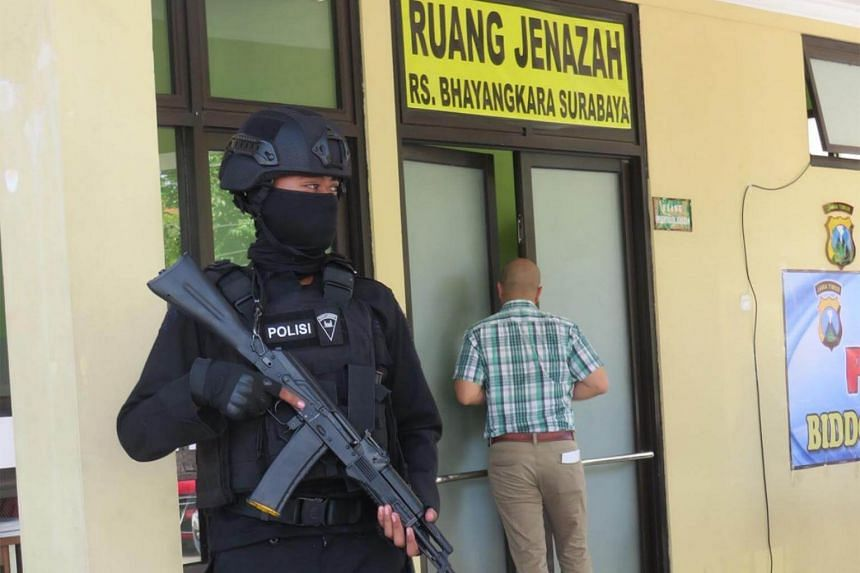 An East Java Police Mobile Brigade (Brimob) officer stands guard in front of the mortuary where bodies of victims and perpetrators of the suicide bomb attacks are held at Bhayangkara Ngagel Hospital in Surabaya, East Java.