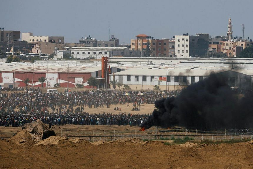 Smoke rises in front of Palestinians who protest against US embassy's move to Jerusalem ahead of the 70th anniversary of Nakba, at the Israel-Gaza border, on May 14, 2018.