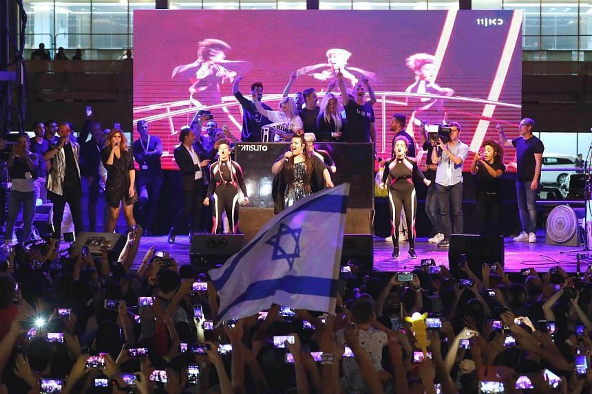 Israel's Netta Barzilai (centre) performs at a festive welcome concert in the Israeli coastal city of Tel Aviv on May 14, 2018.