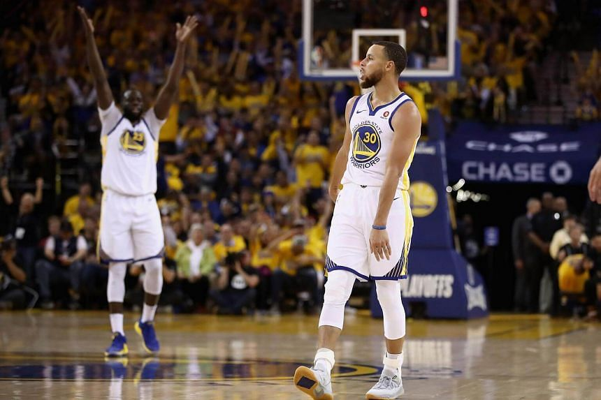 Stephen Curry of the Golden State Warriors and Draymond Green react against the New Orleans Pelicans during Game Five of the Western Conference Semifinals of the 2018 NBA Playoffs, on May 8, 2018.