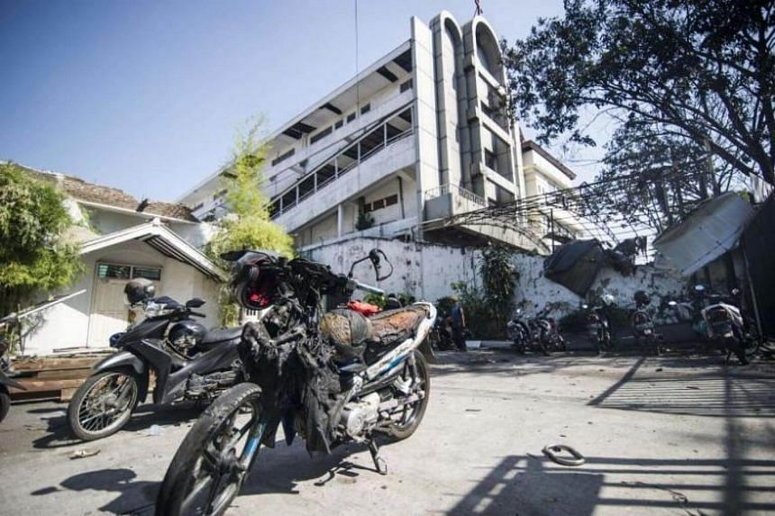 A damaged motorcycle is seen outside the Surabaya Centre Pentecostal Church in Surabaya, Indonesia, on May 14, 2018, following a blast outside the church a day earlier.