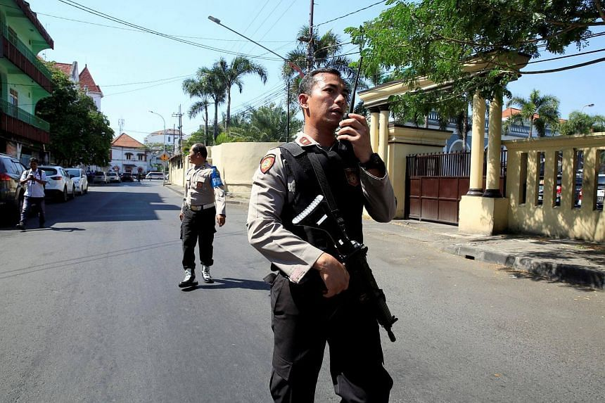An policeman stands guard on a street following a bomb blast at a police station in Surabaya, Indonesia, on May 14, 2018.