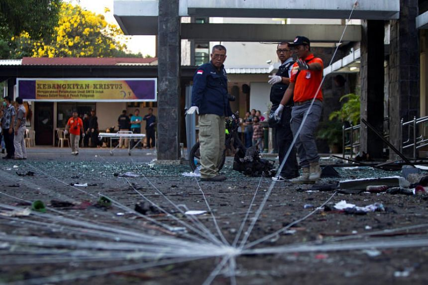 Indonesia's police forensic team examine the scene of a bomb at a church in Surabaya on May 13, 2018.