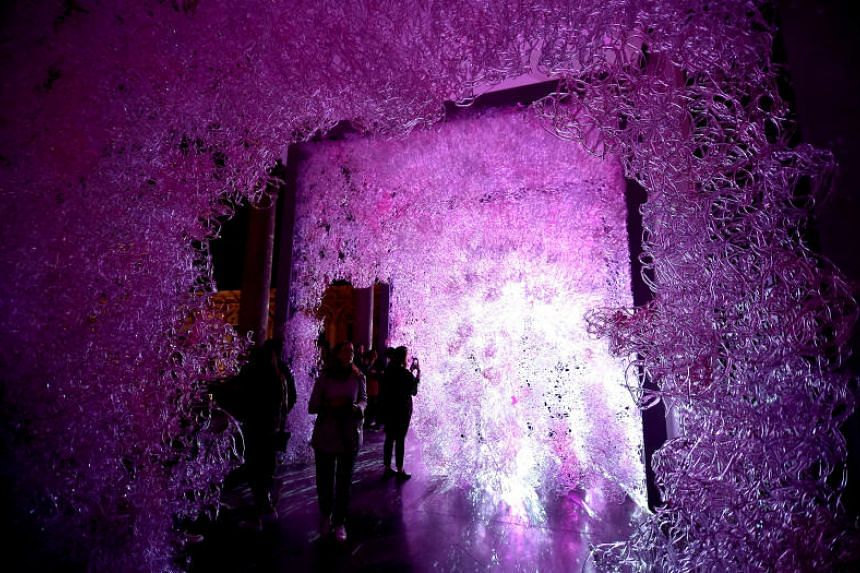 People visit an airborne labyrinth of polycarbonate installation called Limbo, created by Jacopo Foggini, during Design Week in Milan, on April 17, 2018.
