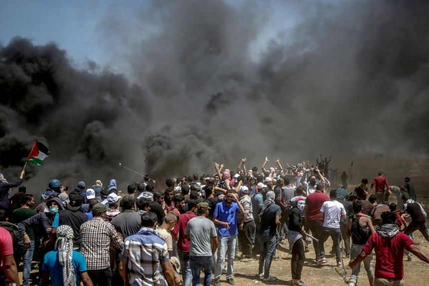 Palestinians take part in clashes after protests broke out near the border with Israel in the east of the Gaza Strip, on May 14, 2018.