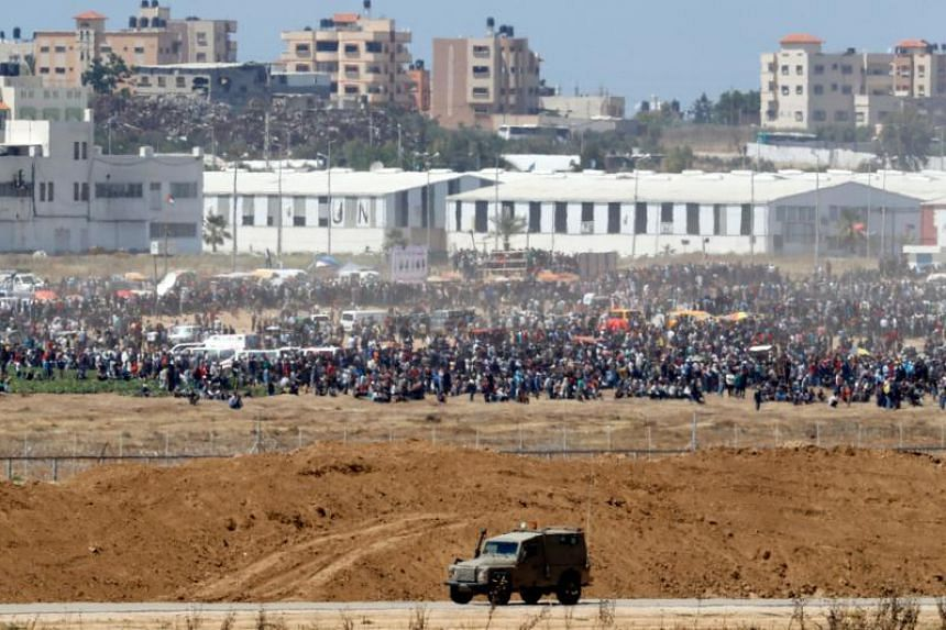 Palestinian protestors gather along the border fence with Israel on May 14, 2018.