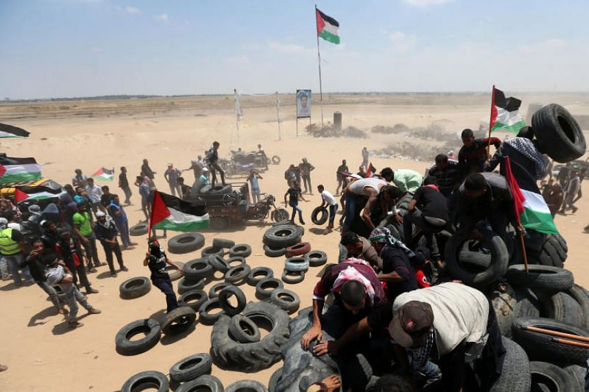 Palestinians collect tires to be burnt during a protest marking the 70th anniversary of Nakba, at the Israel-Gaza border in the southern Gaza Strip, on May 15, 2018.