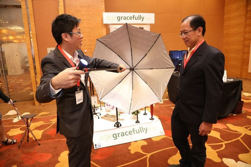 Director of local start-up Bekind Solutions Tan Lee Tuan (left) demonstrating the smart walking stick called 'Bond', which is an umbrella and walking cane combined with other built-in functions.