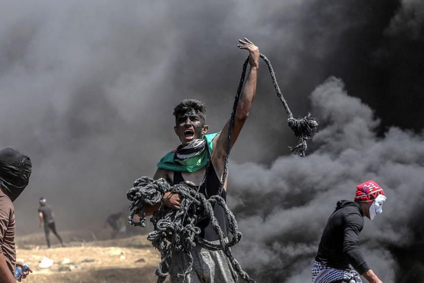 A Palestinian protester holds a rope during clashes after protests near the border with Israel in the east of Gaza Strip, on May 14, 2018.