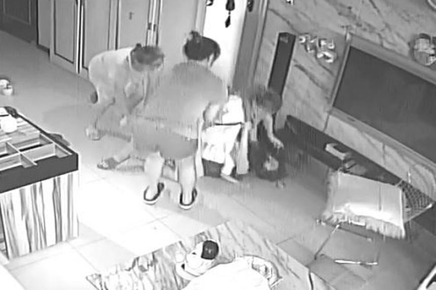 Closed-circuit television footage shows a woman slapping another and tackling her to the ground in a living room.