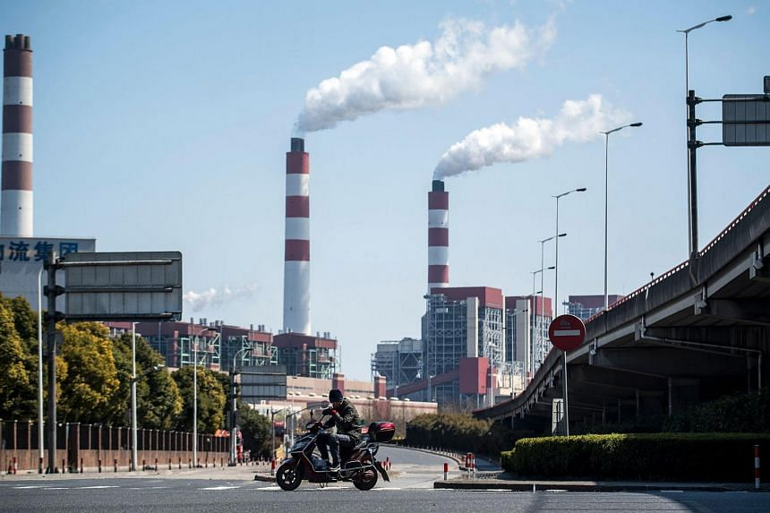 A man riding his scooter near the Shanghai Waigaoqiao Power Generator Company coal power plant in Shanghai.