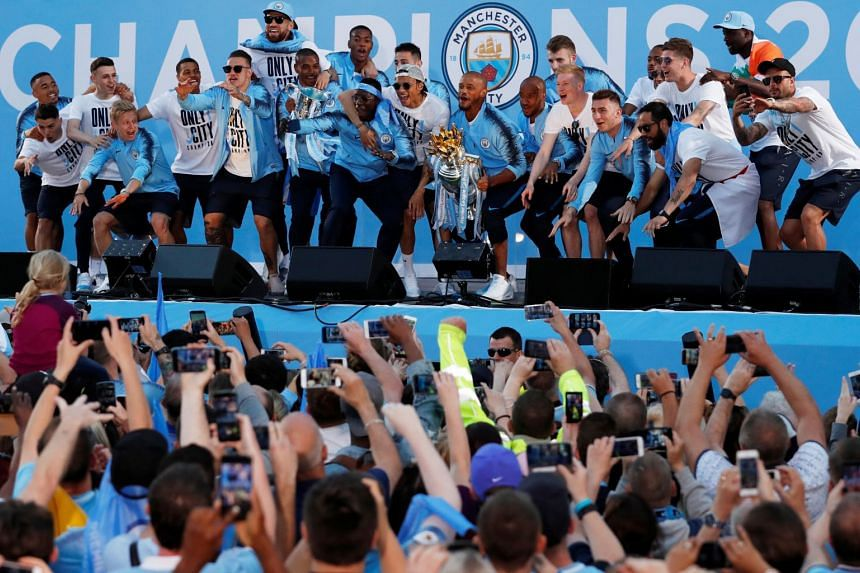 Manchester City's Vincent Kompany lifts the Premier League trophy during the parade.