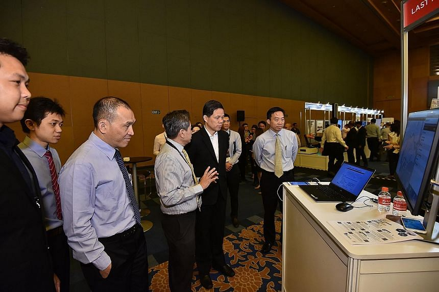 A*Star chairman Lim Chuan Poh (left), Trade and Industry Minister Chan Chun Sing (in jacket) and Enterprise Singapore chief executive Png Cheong Boon (right) viewing exhibits at the SME Technology and Innovation Day yesterday. Mr Chan said more than