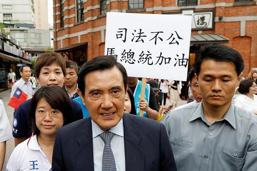 """A Kuomintang member holding a placard reading, """"Injustice, President Ma cheer up"""" yesterday as former president Ma Ying-jeou leaves an event in Taipei. The High Court overturned a lower court's not-guilty ruling and sentenced Ma to four months' jail"""
