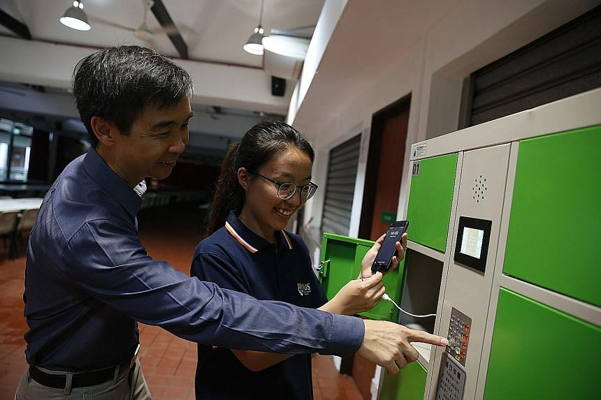 (Far left) Dr Zhang Jingxin blending the food before it goes into the anaerobic digester. (Left) Prof Tong Yen Wah shows student Gu Danning how the food-waste powered charging station in NUS' Raffles Hall works.