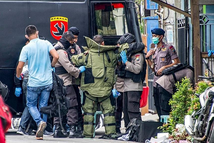 A police officer standing guard as a raid was carried out at the house of a suspected terrorist in Surabaya yesterday.
