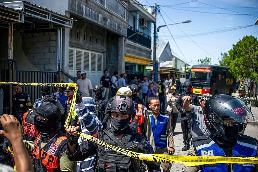 Police cordoning off an area during one of the raids in Surabaya yesterday. Bombings were carried out at three churches in the Indonesian city on Sunday and another took place at the police headquarters on Monday.