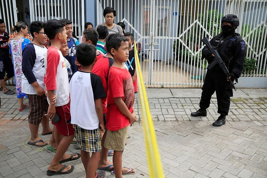 An officer putting on a protective suit in Surabaya yesterday. Police said 13 people were nabbed and two others killed in the raids.