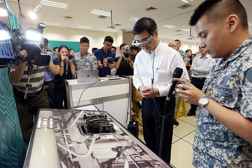 Senior Minister of State for Defence Heng Chee How trying out a smart maintenance system using augmented reality with the help of Military Expert 5-1 Aw Chee Giap (right) yesterday.