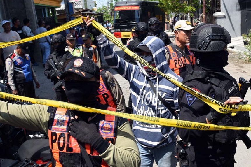 Anti-terror police officers secure the area during a raid at the house of a family said to have carried out bombing attacks, in Surabaya, Indonesia, on May 15, 2018.