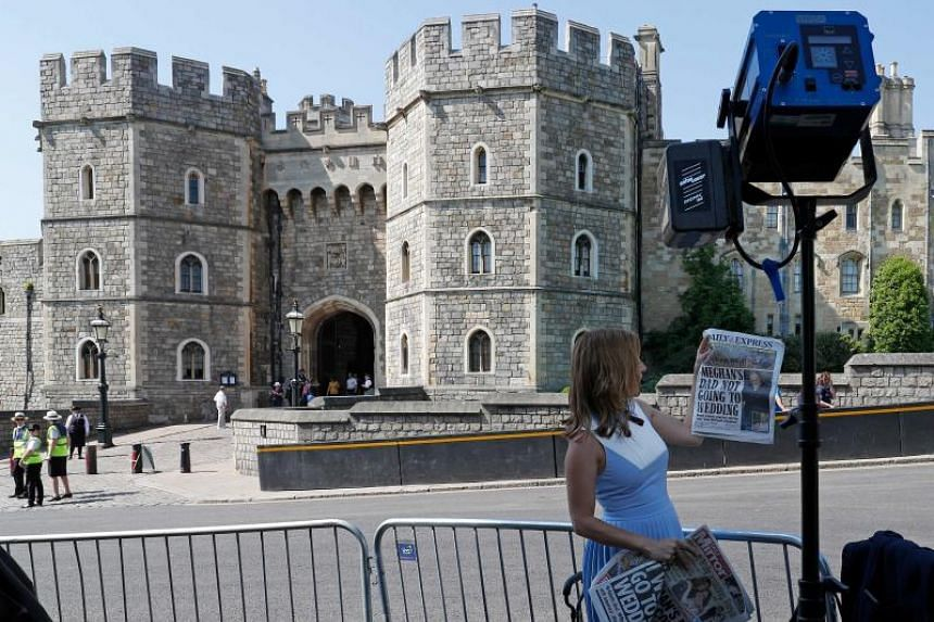 A television reporter holds up copies of British newspapers leading with a story of Meghan Markle's father Thomas Markle, opposite the Henry VII Gate of Windsor Castle in Windsor, west of London on May 15, 2018.