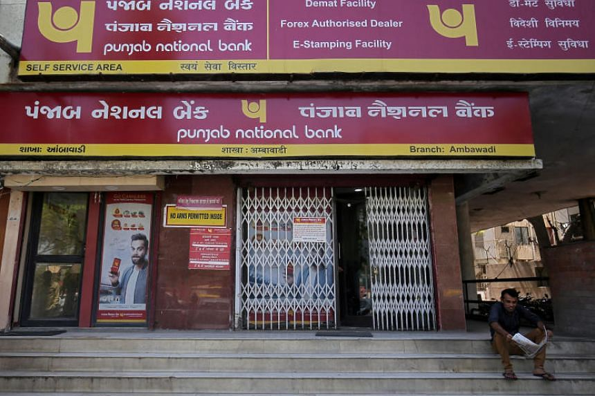 A man reads a newspaper outside a branch of Punjab National Bank in Ahmedabad, India.