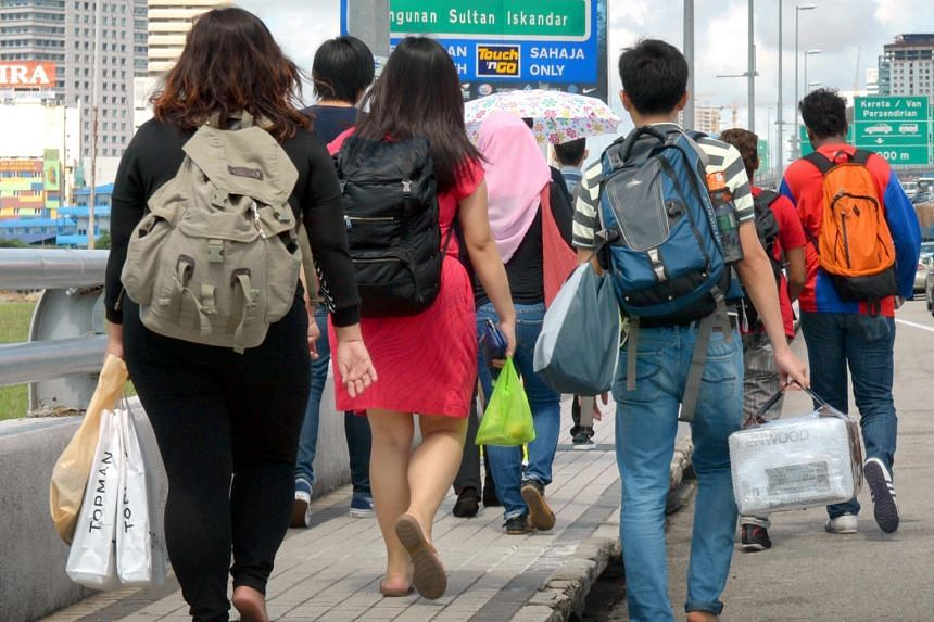File photo showing people carrying shopping bags while walking beside a congested road in Johor Baru.