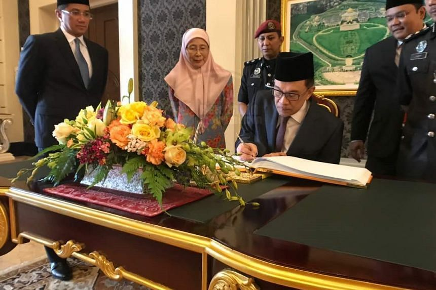 Mr Anwar Ibrahim (seated) and Deputy Prime Minister Wan Azizah Wan Ismail at the palace, where he has been granted an audience with the King at noon.