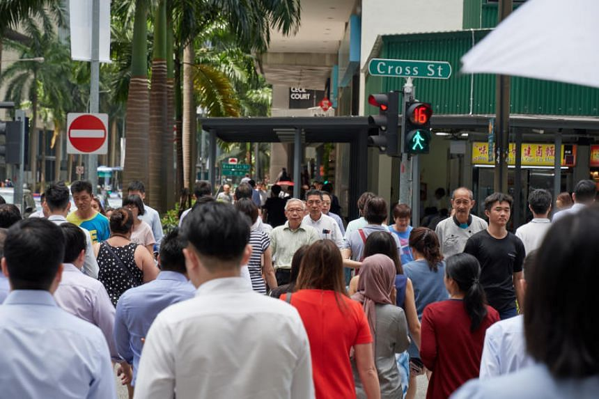 File photo showing pedestrians crossing the road in Singapore's central business district on March 19, 2018.