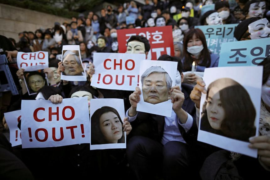 People hold portraits depicting Korean Air Lines' chairman Cho Yang Ho and his daughters Cho Hyun Ah and Cho Hyun Min as they take part in a protest against the abuse of power by them, in central Seoul, South Korea, on May 4, 2018.