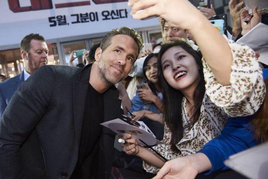 Deadpool 2 star Ryan Reynolds takes a selfie with a fan in Seoul.